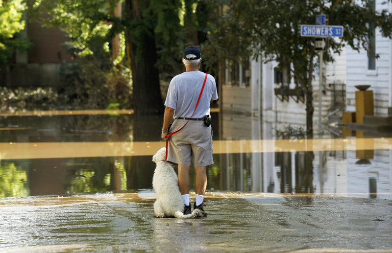 John Wimer and his dog, Carlie, go out Saturday to look at flooding caused by Tropical Storm Lee in Harrisburg, Pa.