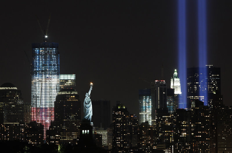 The Tribute in Light, visible at right, an art installation representative of the twin towers, shines above the altered lower Manhattan skyline that includes the Statue of Liberty and the new One World Trade Center, left.