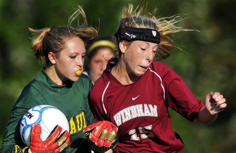 Gabe Souza/Staff Photographer Mc Auley keeper Molly Miller secures the ball while fighting off Windham's Mary Margaret Green during their SMAA girls' soccer game Monday in Portland. Windham won, 3-0.