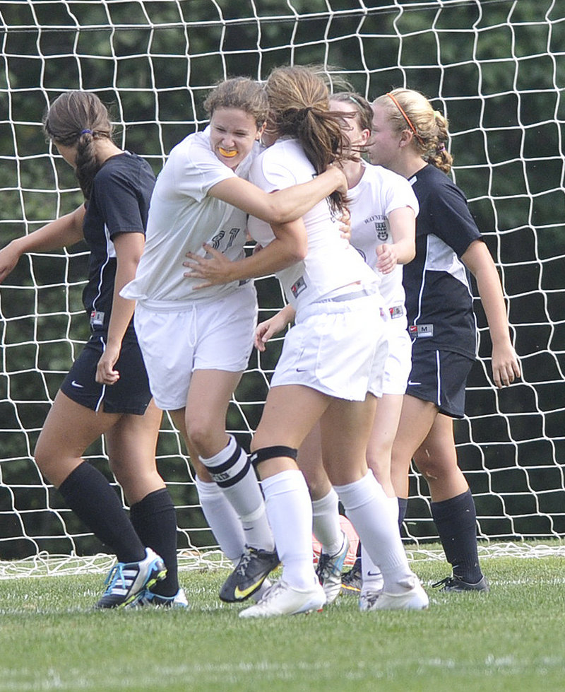 Becky Smith of Waynflete, left, hugs teammate Ella Millard after Millard scored the first goal Wednesday of an 8-0 victory against North Yarmouth Academy in Portland. Smith finished with two goals for the Flyers, who improved to 2-1. NYA is 0-4.