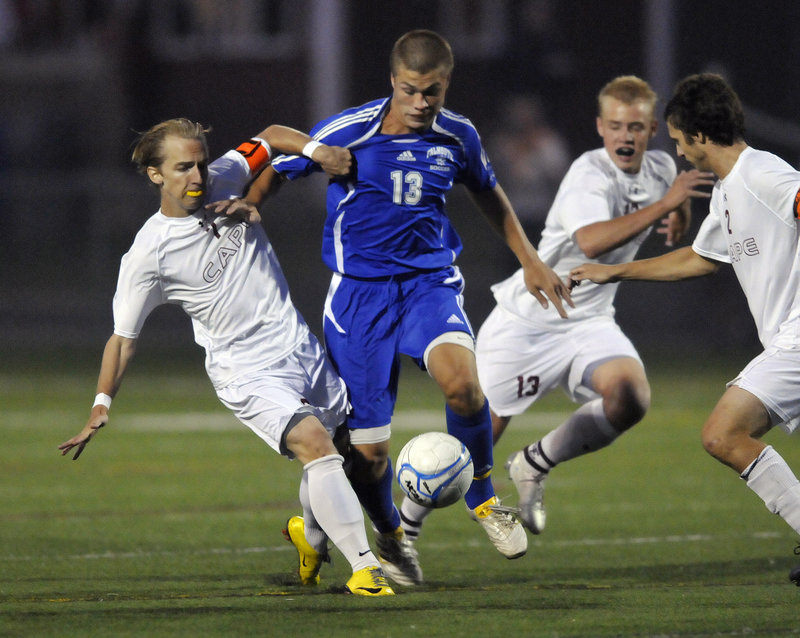 Brandon Tuttle, center, tries to maneuver between Cape Elizabeth's Blake Barritt, left, and Griffin Thoreck during a boys' soccer game Wednesday night at Cape Elizabeth. Falmouth improved to 3-0 with a 2-1 victory.