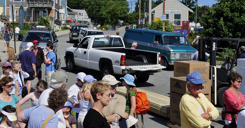 In a 'Peaks Island rush hour,' people and vehicles line up to board the ferry to the mainland. A reader wonders if perhaps, compared to other Maine island property owners, he might be paying too much for the privilege.