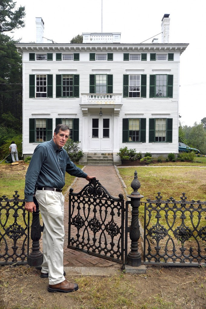 Maine Preservation Executive Director Greg Paxton shows off the restored cast-iron fence.