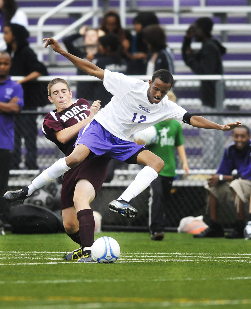 Abdirizaq Hassan of Deering competes for the ball Thursday night against Jake Emard of Noble during their schoolboy soccer game. Deering won 2-0 at home in its first outing since one of its players, Mohamed Hassan, drowned last weekend.