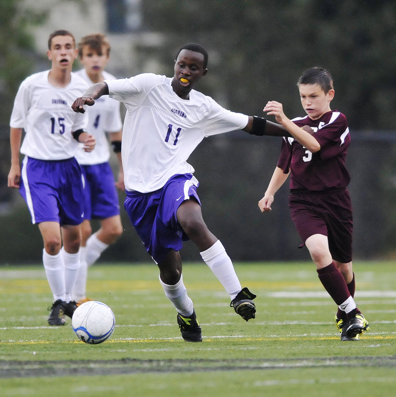 David Ndayshimye of Deering attempts to control the ball and break away while holding off Josh Emard of Noble during their Western Class A schoolboy soccer game Thursday night. Deering won, 2-0.