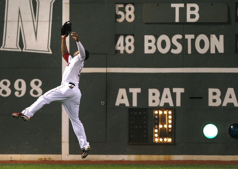 Carl Crawford of the Boston Red Sox leaps to the warning track in left field to haul in a drive by B.J. Upton of the Tampa Bay Rays in the fifth inning of Tampa Bay's 9-2 victory Thursday.