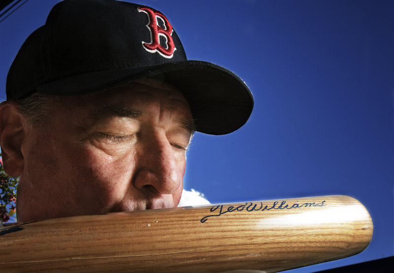 Bud Elwin kisses a bat signed by Ted Williams. A longtime supporter of Healthy Kids Damariscotta, Elwin is raffling off memorabilia to help the nonprofit after a loss of state funding.