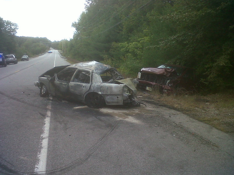 Vehicles involved in a four-car accident rest on the side of Route 302 in Raymond on Friday. The crash injured two men and remains under investigation.
