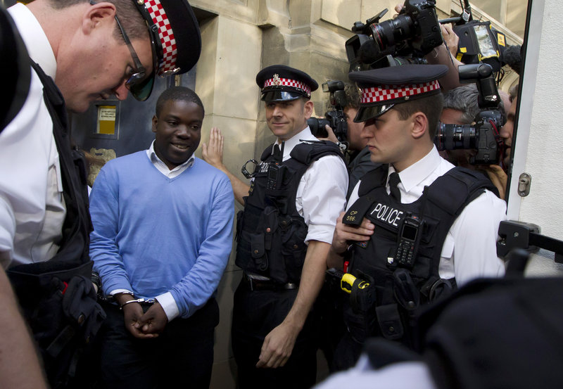 Alleged rogue UBS trader Kweku Adoboli, flanked by police officers, walks toward a security van to be taken to jail Friday after appearing at the City of London Magistrates Court.