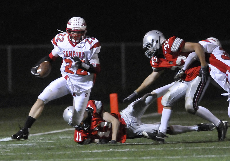 Alex Shain, who scored three touchdowns for Sanford, eludes one tackle and looks for more room in the game at South Portland.