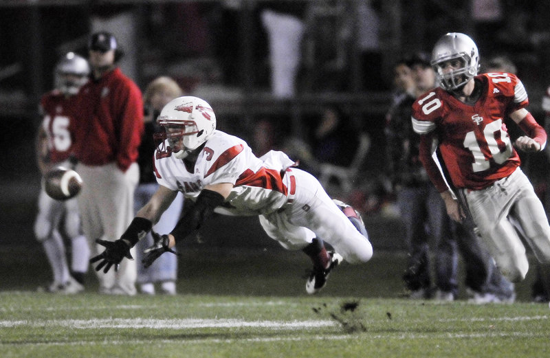 Jon Schroder of Sanford dives in an attempt to make a catch Friday night as Michael Salvatore of South Portland moves in on defense. South Portland came away with a 42-34 victory in a Western Class A game.