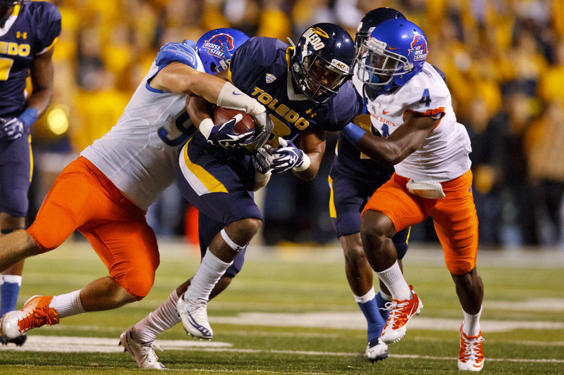 Eric Page of Toledo, center, is tackled by Boise State's Byron Hout, left, and Jerrell Gavins after a reception Friday night. Fourth-ranked Boise State won, 40-15.