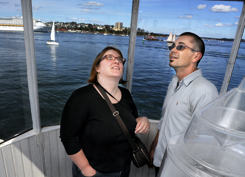 Bronwyn and Sean Dougherty of Oakland check out the inside of the top of Bug Light in South Portland on Saturday. A cruise ship is visible in Portland Harbor at left.