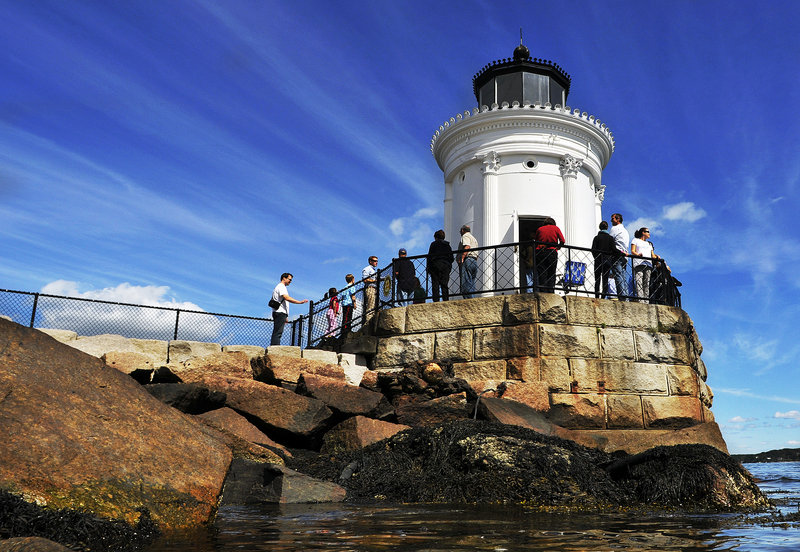 People gather around Bug Light in South Portland on Saturday during Open Lighthouse Day, when lighthouses along the coast are open to visitors.