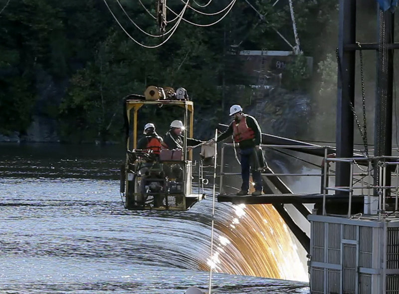 Tyler Grant hands boots to Mitch Simpson before returning to shore in a cable car with Kevin Gallant at Veazie Dam on the Penobscot River in Veazie. The Department of Marine Resources workers were checking for salmon in a cage, at the bottom right, which is at the top of a fishway.