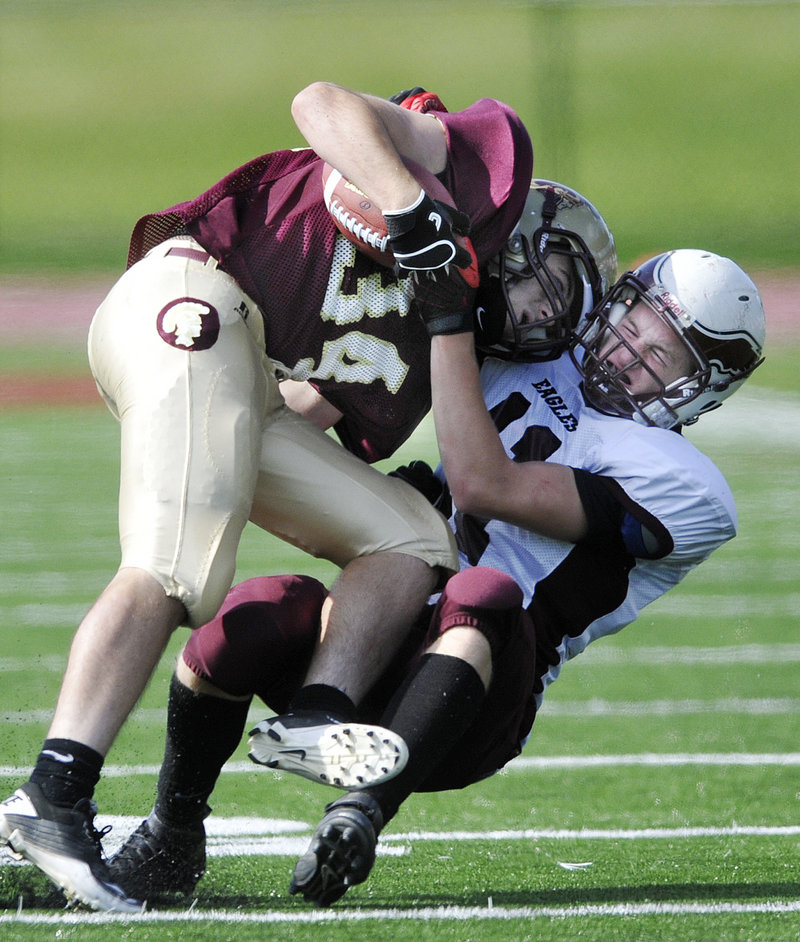 Nick Kenney of Thornton Academy is dragged down by Todd Allen of Windham during their defensive struggle Saturday. Thornton won 7-0 on a first-period touchdown.