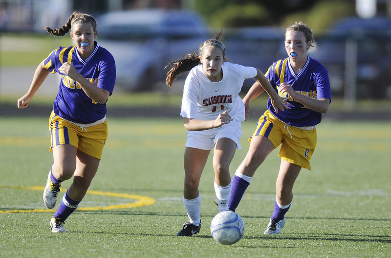 Photos by Shawn Patrick Ouellette/Staff Photographer Taylor Leborgne of Scarborough, center, attempts to get to the ball ahead of Leeann Morrison, left, and Eden Monsen of Cheverus during their schoolgirl soccer game Saturday. The teams finished in a 1-1 tie at Scarborough High.