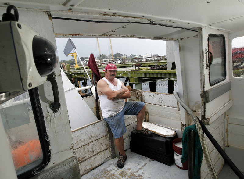 Bill Skrobacz sits on his fishing boat in Gloucester, Mass., as a camera, left, is positioned to observe him and his crew as they work. He volunteered to test the system.