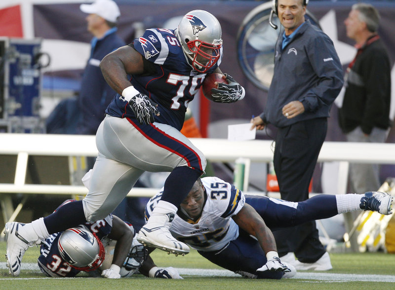 Patriots defensive lineman Vince Wilfork rumbles past San Diego running back Mike Tolbert on his 28-yard return after intercepting Chargers quarterback Philip Rivers' pass Sunday in Foxborough, Mass. The play set up a 47-yard field goal and a 13-0 Patriots lead.
