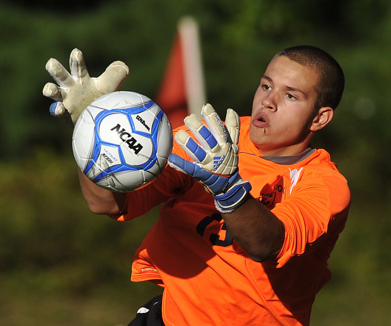 Westbrook goalkeeper Austin Blake keeps his eye on the ball as he makes a save on a shot by Sanford during their SMAA boys' soccer match Monday afternoon in Westbrook. Blake finished with six saves as the Blue Blazes beat the Redskins, 4-2.