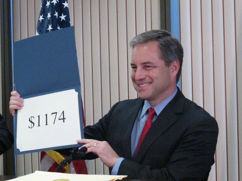 Alaska Gov. Sean Parnell reveals the amount of this year's Permanent Fund Dividend checks Tuesday in Juneau.