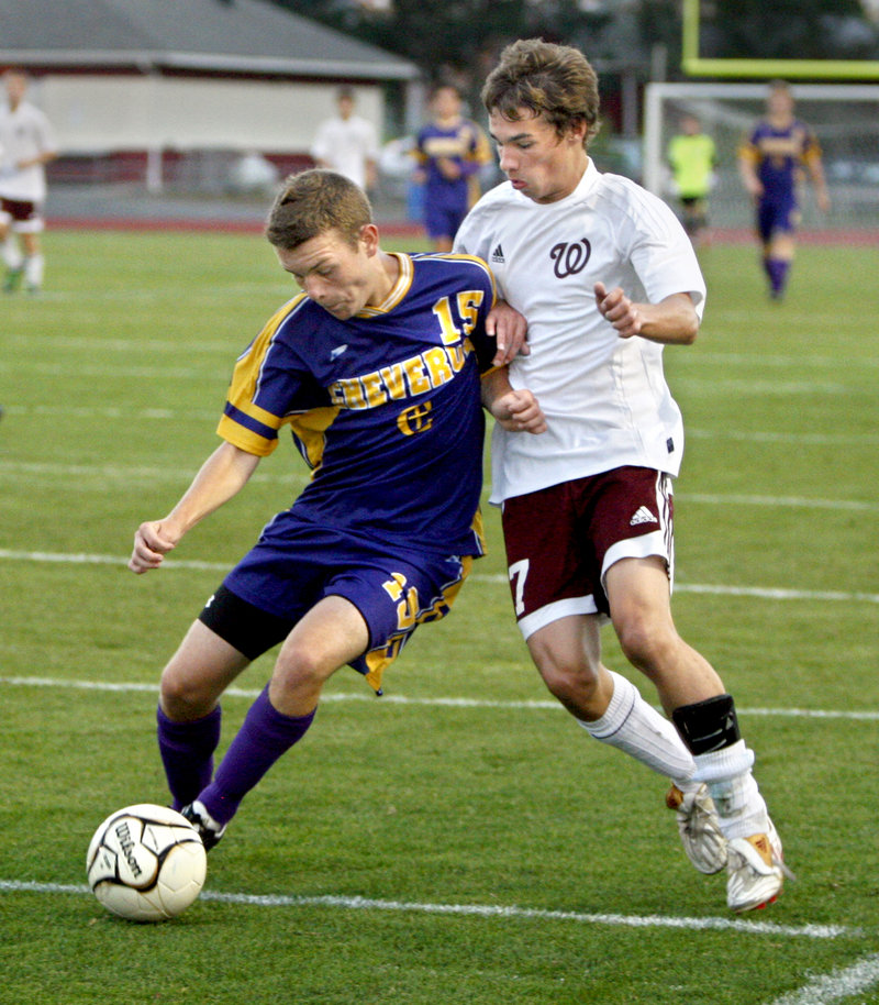 Nate Palmer of Cheverus attempts to control the ball while holding off Marc Reynolds of Windham during Cheverus' 2-0 victory Tuesday night at Windham High.