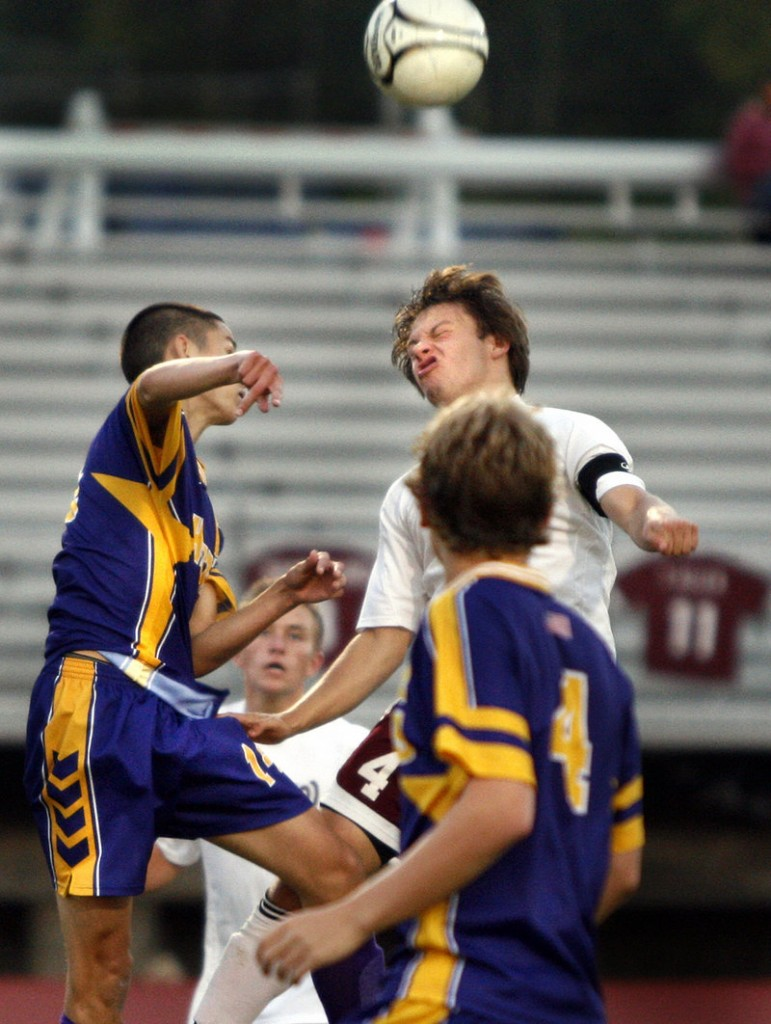 Robbie Lentine of Windham gives the oomph on a header while directing the ball past Bill Risigo, left, and Jacob Smith of Cheverus during Cheverus' 2-0 victory in a boys' soccer game Tuesday.