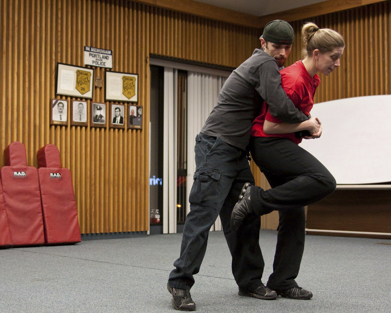 Coreena Behnke, a Portland police officer and an instructor for the Rape Aggression Defense program, demonstrates a self-defense technique with Richard Sparrow, also an instructor, during a recent class.