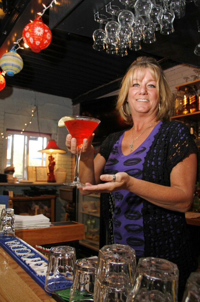 Linda Gaudet serves a cocktail at Jumpin' Jakes Seafood Cafe, where the weekday happy hours are a real treat.