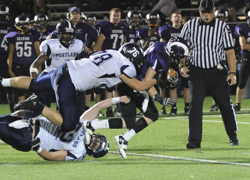 Trey Thomes of Deering is brought down by Cristian Doughty, 52, and Kyle Reichert, 78, of Portland during Deering's 28-7 victory Friday night. Thomes ran 51 yards with a blocked punt early in the second quarter for the first touchdown of the game.