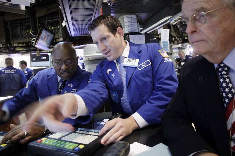 Barclays Capital employees Vincent Folds, left, William Bott, center, and James Maguire work at the New York Stock Exchange on Friday, when the Dow Jones industrial average rose 37.65 points.