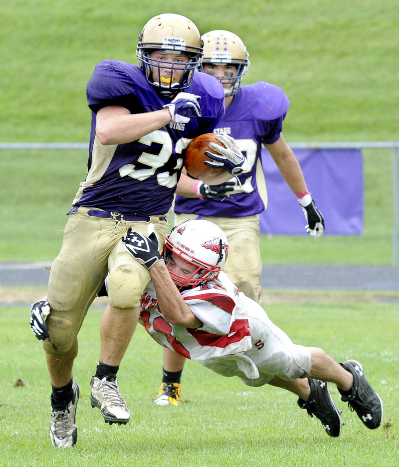 Brent Green of Cheverus shakes off Jake Dexter of Sanford to pick up yardage Saturday during unbeaten Cheverus' 41-8 victory at home. The Stags, seeking a second straight Class A championship, are 4-0. Sanford dropped to 2-2.