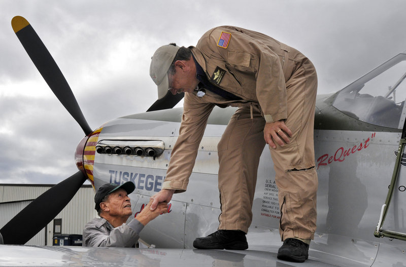 Jim Sheppard shakes hands with Doug Rozendaal of the Commemorative Air Force Red Tail Squadron, which travels the country teaching the history of the Tuskegee Airmen.