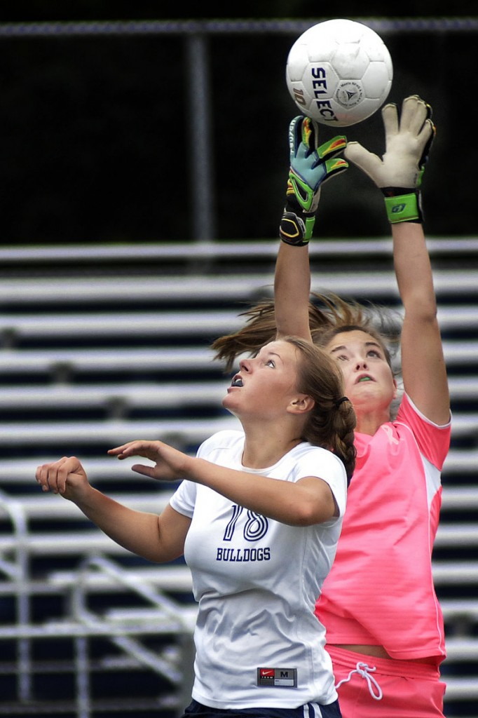 Maris Butler, the goalkeeper for Bonny Eagle, goes high to grab the ball over Ashley Frank of Portland.