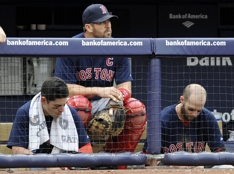 Jacoby Ellsbury, left, Jason Varitek, center, and Dustin Pedroia reflect the mood in the dugout during their first game Sunday in New York. The Yanks won the opener, 6-2.