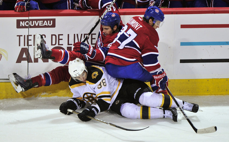 Montreal's Mike Blunden, rear, and Gabriel Dumont fall over Boston's Jordan Caron in an NHL exhibition in Montreal.