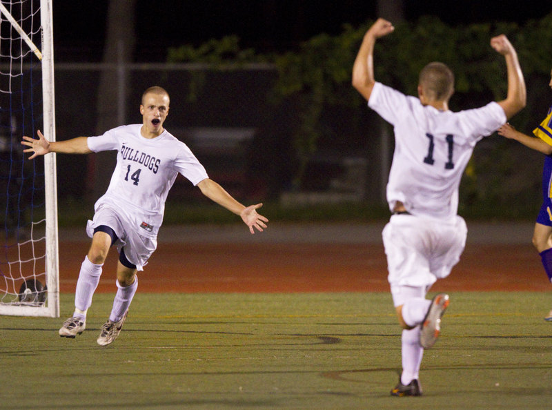 Tim Rovnak, left, celebrates with teammate Paley Burlin after scoring the overtime goal that gave Portland a 3-2 victory against Cheverus on Tuesday night at Fitzpatrick Stadium. Rovnak scored all of the goals for the Bulldogs, who improved to 6-1-1.