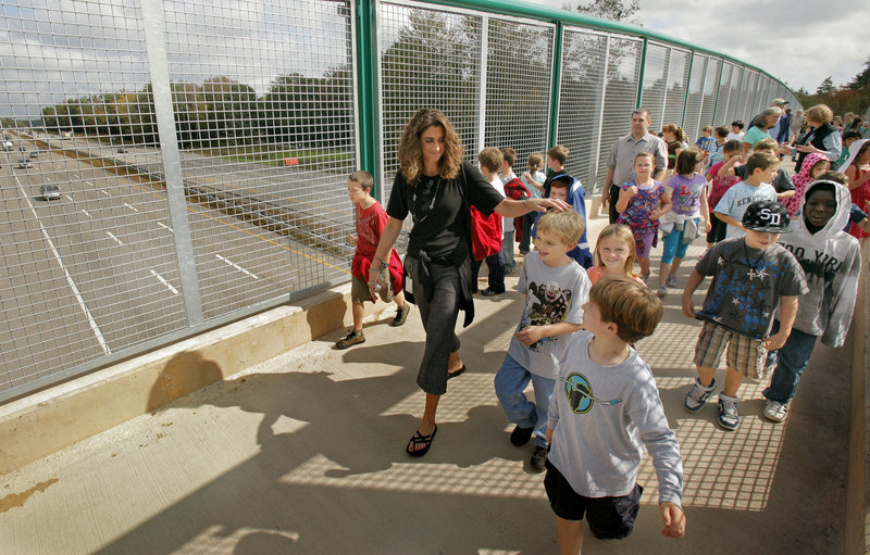 """Third-grade teacher Heather Keep leads some of the nearly 500 elementary school pupils crossed the new Eastern Trail bridge over the Maine Turnpike in Kennebunk on Wednesday to help dedicate the structure. John Andrews, founder of the Eastern Trail Alliance, said getting the bridge built was the """"biggest challenge"""" for trail supporters. The bridge, solely for the use of pedestrians and cyclists, is the first of its kind spanning the turnpike."""