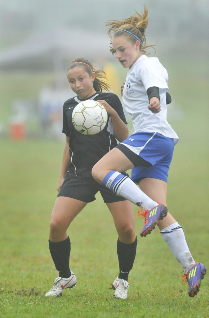 Olivia Dubois of Old Orchard Beach, right, knocks down a pass with her knee Thursday while defended by Hannah Twombly of North Yarmouth Academy. Old Orchard won, 5-0.
