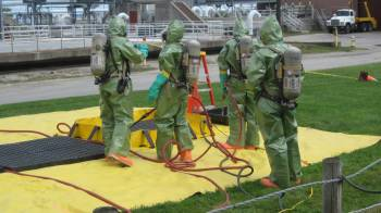 Members of the decontamination team work on the scene at Portland's wastewater treatment plant late Tuesday afternoon.