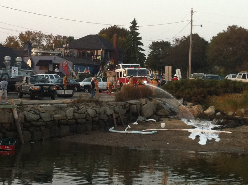Firefighters spray foam onto the beach and the water near Cape Porpoise pier in Kennebunkport after a pickup truck was pulled from the water Saturday evening.