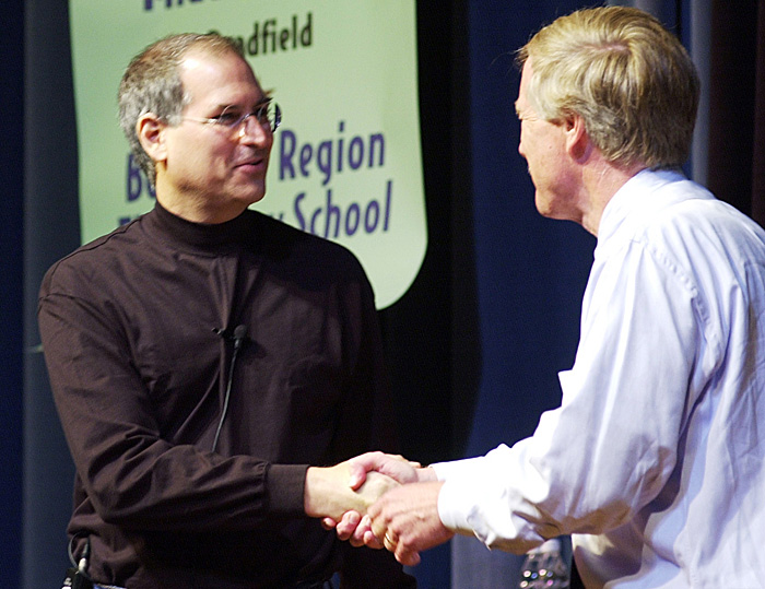 In this June 10, 2002, Steve Jobs, founder and then-president of Apple Computer is greeted by Gov. Angus King as he is introduced at the governor's laptop computer assessment program before educators, legislators, students and others at Portland High School. Apple ibook laptops were the exclusive laptops bought for the students and Apple provided financial and technical support for the program.
