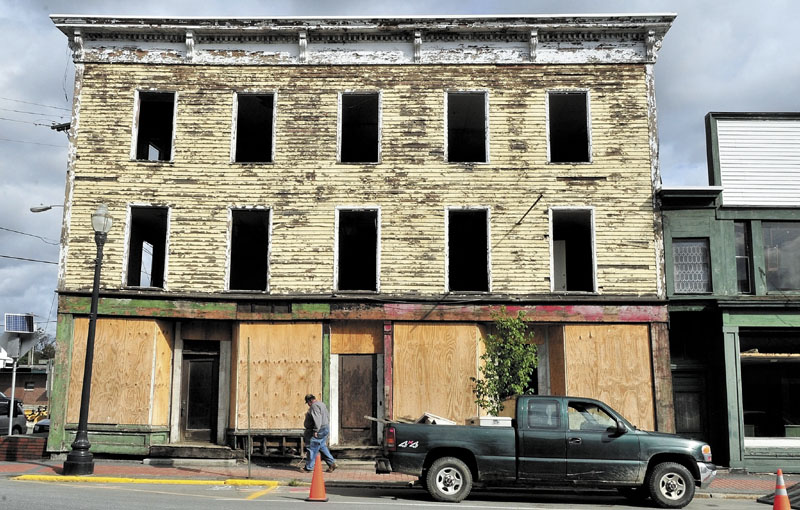 EYESORE: Alan Griffeth walks past the Sweet Memories of Maine building at the corner of Madison Ave. and Commercial Street in Skowhegan where he and demolition crews are removing windows, wiring and plumbing before the building and two others will be torn down this fall.