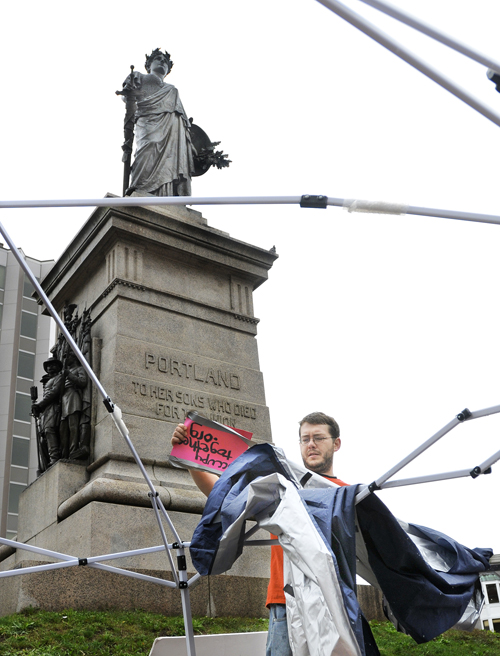 John Rasmussen, 27, who said he arrived in Portland last week and joined protests against Wall Street in Monument Square, packs up a tent after Portland police ordered demonstrators to take it down today.