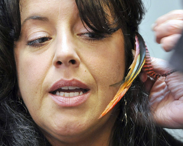 Stylist Tracie Goriss eyes the rooster feather she was having put in her hair Thursday at Studio 114 in Westbrook.