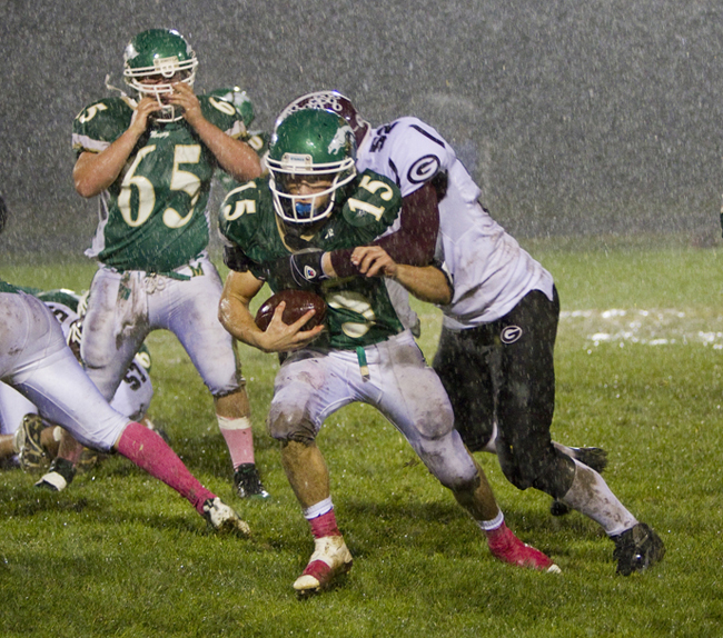 Massabesic quarterback Jake Desrochers attempts to slip past Kyle Nealey of Gorham during their game on a muddy field Friday night. Gorham outscored the Mustangs, 63-47.