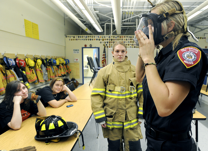 Westbrook High School freshmen Mackenzie Souza and Paige Fogg watch Westbrook firefighter and paramedic Rachael Welch demonstrate gear she wears to a fire as Westbrook Regional Vocational Center hosted the Totally Trades Conference.