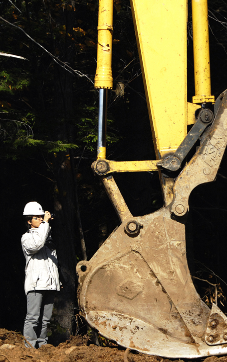 Ohchi Shunsuke photographs a bucket loader Monday. In Miyazaki Prefecture, on the island of Kyushu, loggers harvest the evergreen Cyryptomeria Japonica, known as sugi, and the cypress Chamaecyparis obtusa, known as hinoki, which are used for housing. Miyazaki foresters have to deal with soggy conditions because the average annual rainfall is 138 inches.