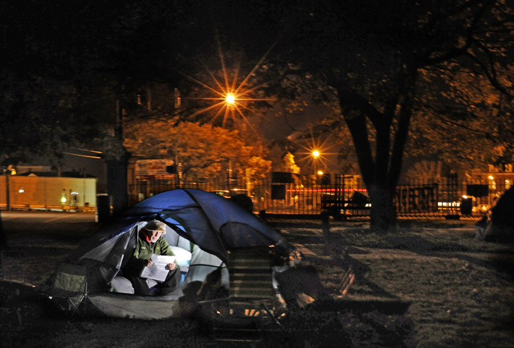 "Occupy Maine participant Robert W. Davis IV, also known as ""Bobby D,"" of Portland, reads a newspaper inside his tent in Lincoln Park on Tuesday night. Davis' tent, which includes a small mattress, nightstand, lamp and other personal effects, is one of about three dozen that have created a small tent city housing Maine's incarnation of the protest movement."