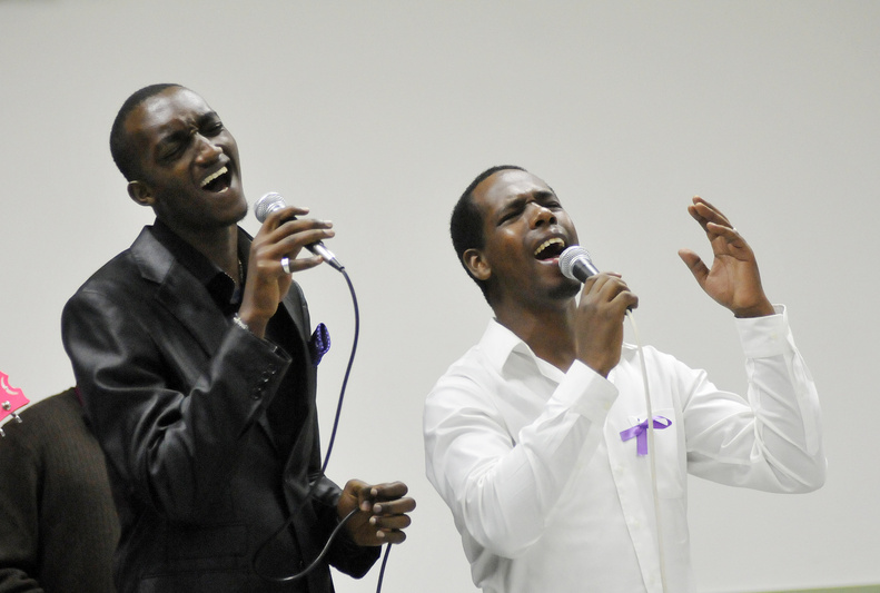Junior Nubu, left, and Bienvenue Tutabara sing during a memorial service Sunday at the St. Pius X Parish Hall in Portland for the seven Tutsi, or Banyamulenge, humanitarian aid workers who were killed in the Congolese province of South Kivu this month. Similar services were held around the world.
